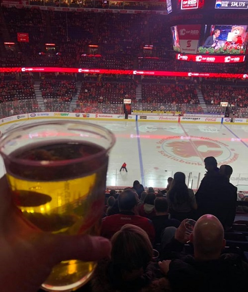 Photo of a Calgary Flames fan drinking beer at Scotiabank Saddledome during a Calgary Flames game.