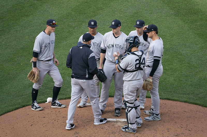 Photo of New York Yankees players meeting on the mound.