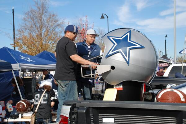 Photo of two Dallas Cowboys fans working the grill outside of AT&T Stadium.