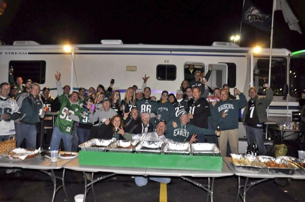 Photo of Philadelphia Eagles fans tailgating at night.