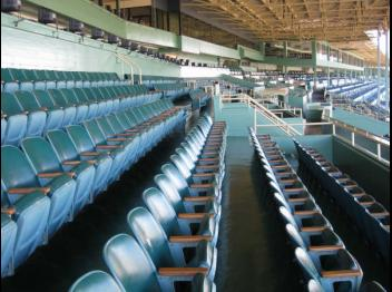 Stock photo of empty seats under a canopy at an outdoor stadium.