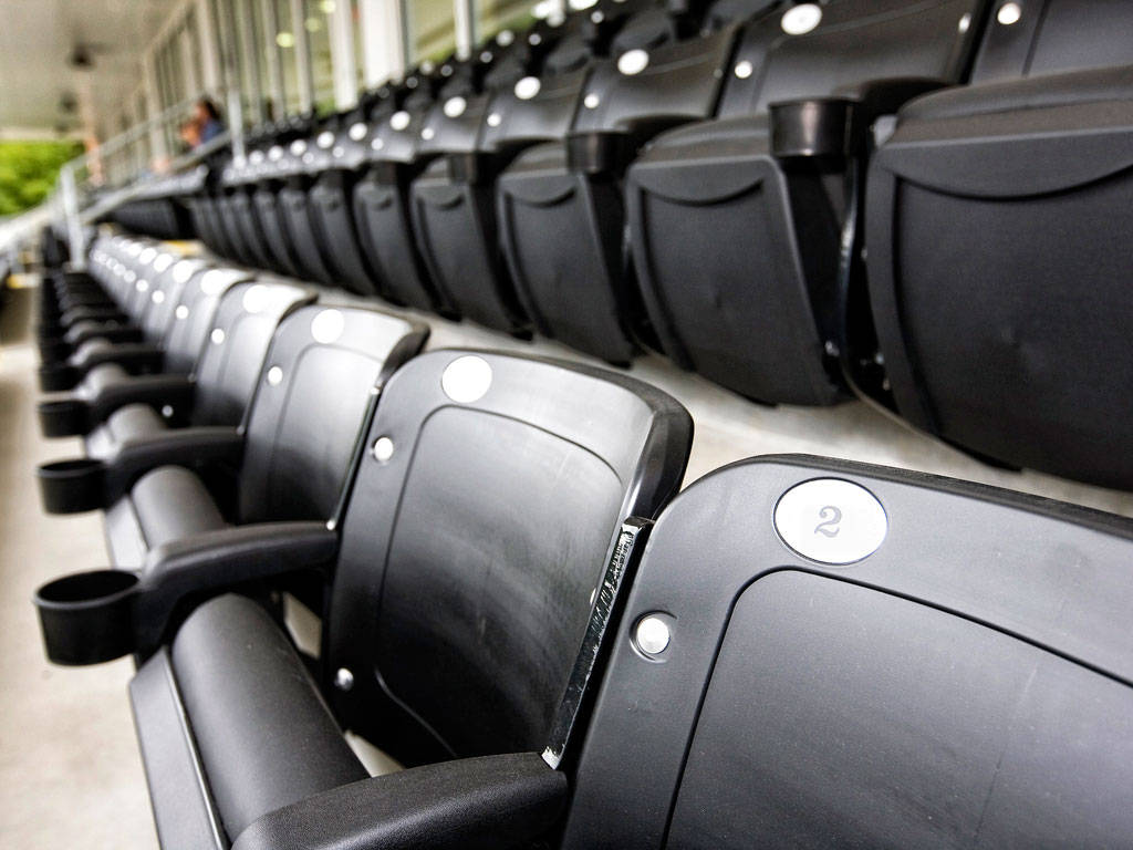 Stock photo of an empty row of stadium seats.