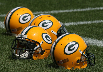 Photo of Green Bay Packers Helmets laying on the field.