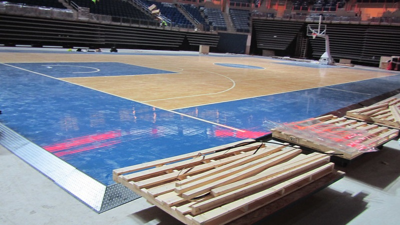 Photo of a basketball court being installed inside an arena.