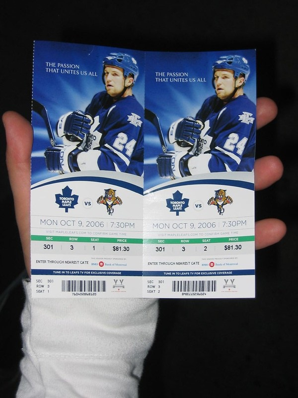 Photo of a hockey fan holding Toronto Maple Leafs tickets.