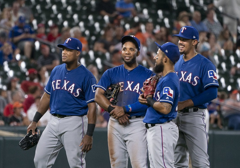 Photo of Texas Rangers players meeting on the pitcher's mound at Globe Life Park in Arlington.